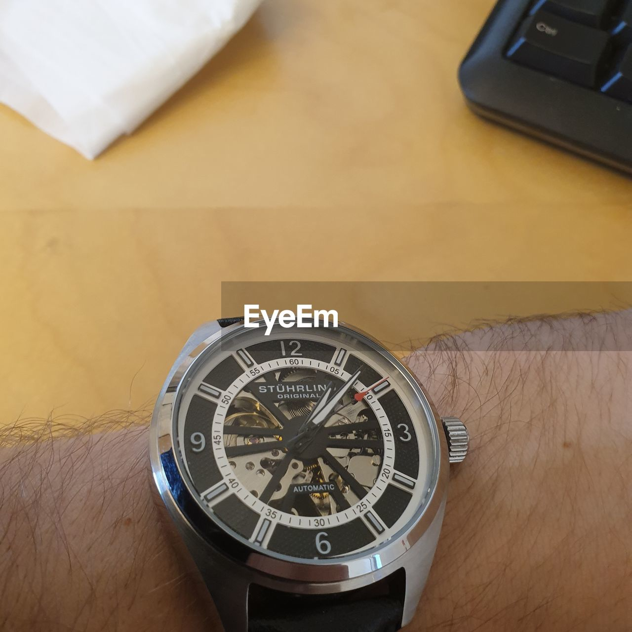 human hand, human body part, hand, time, accuracy, one person, watch, wristwatch, indoors, high angle view, close-up, number, table, real people, technology, communication, wood - material, holding, body part, finger, silver colored, personal accessory