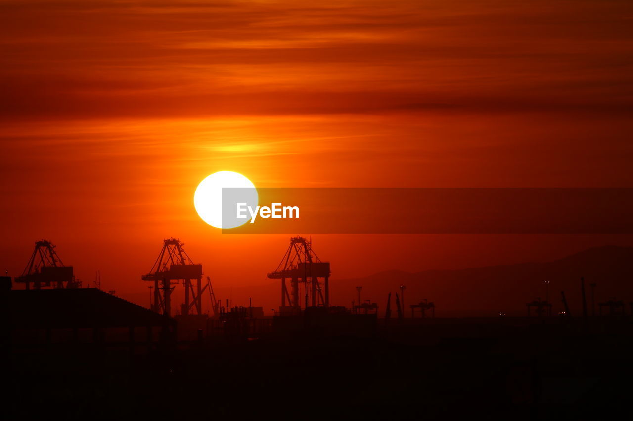 sunset, sky, sun, orange color, silhouette, beauty in nature, scenics - nature, no people, industry, nature, machinery, crane - construction machinery, construction industry, cloud - sky, outdoors, tranquil scene, sunlight, tranquility, architecture, built structure