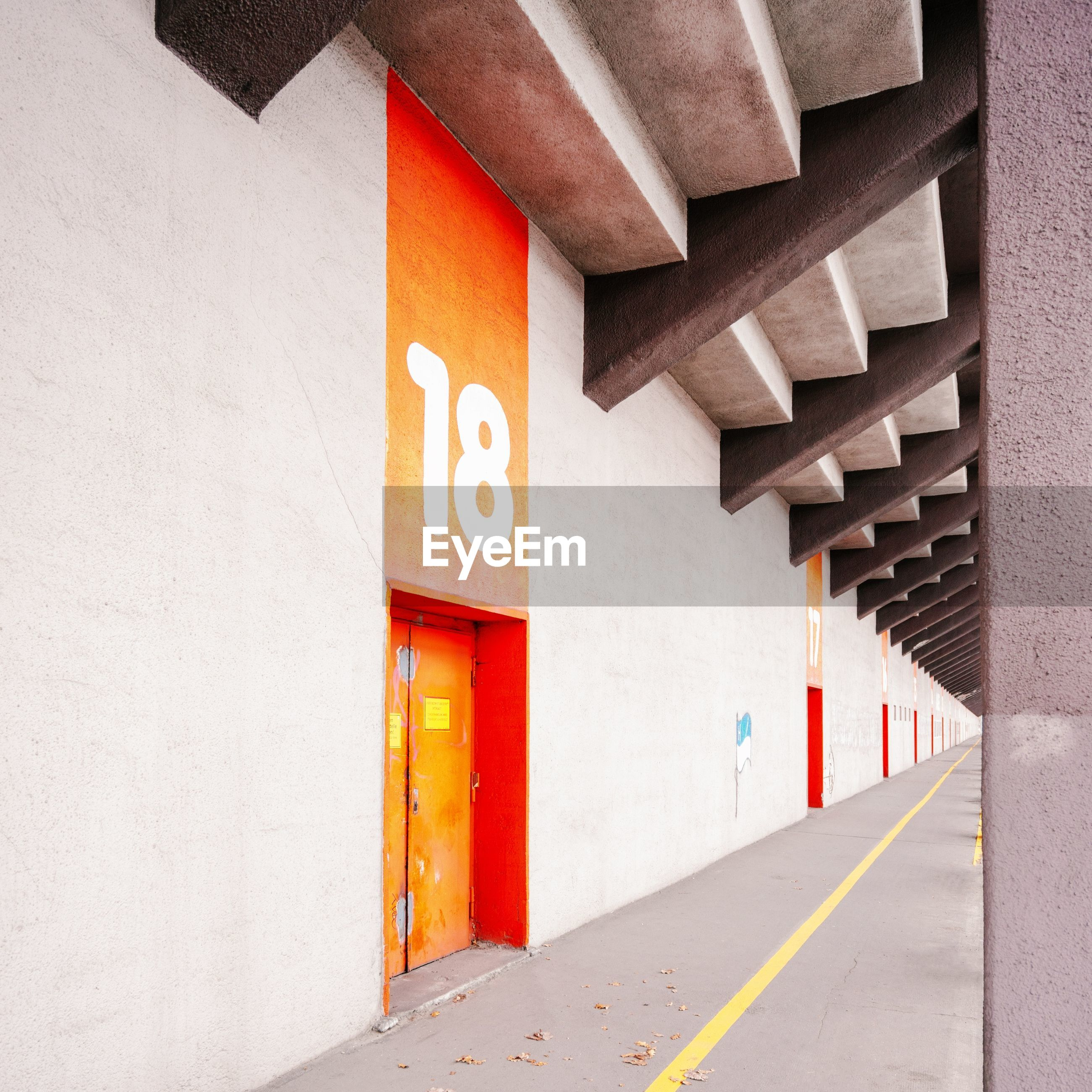 architecture, built structure, sign, no people, communication, direction, building exterior, day, wall - building feature, road, architectural column, number, transportation, building, guidance, the way forward, symbol, outdoors, red, orange color, parking garage, dividing line, ceiling