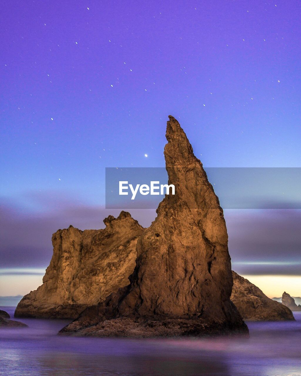 Rock Formation In Sea Against Sky At Dusk