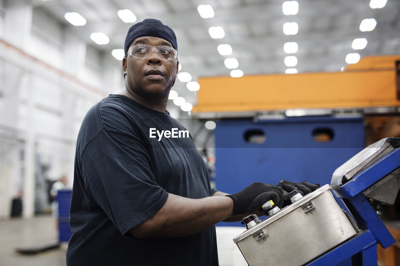 PORTRAIT OF MAN STANDING BY FACTORY