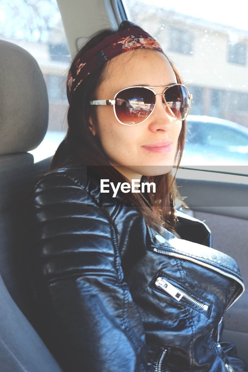Portrait Of Woman In Leather Jacket Wearing Sunglasses While Traveling In Car