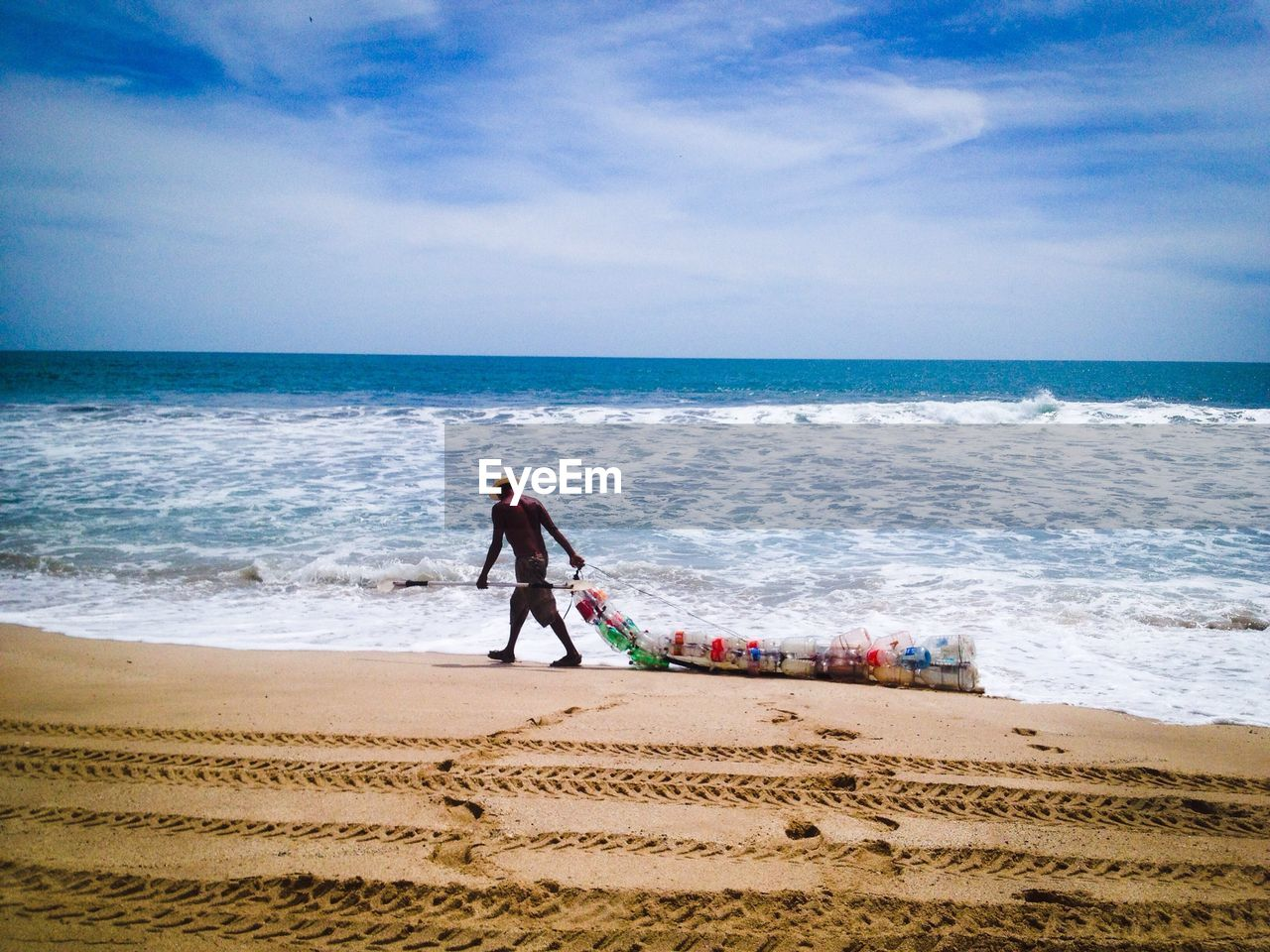 sea, beach, horizon over water, sand, sky, water, shore, nature, one person, real people, day, full length, wave, scenics, walking, beauty in nature, outdoors, standing, leisure activity, vacations, men, people