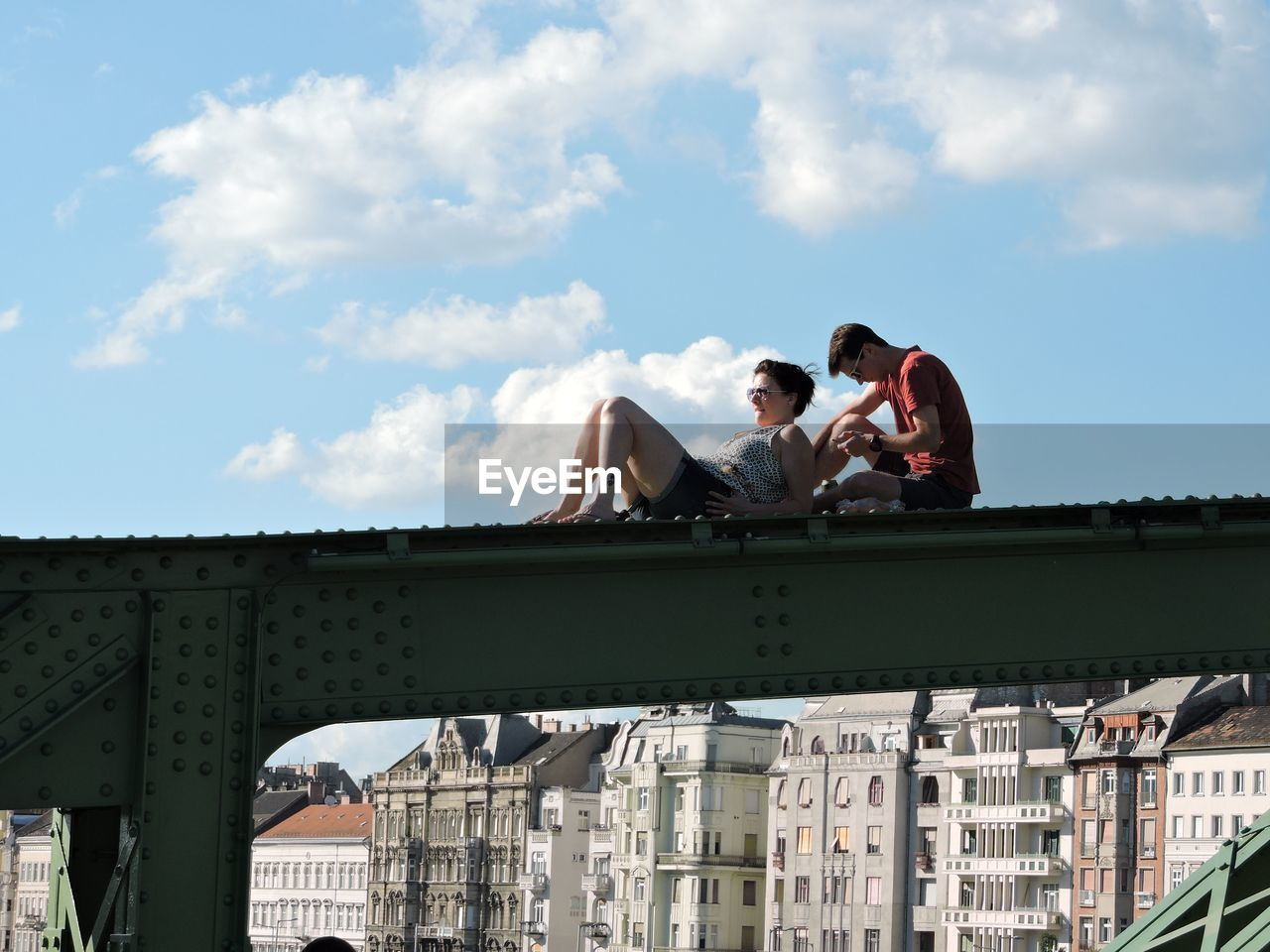 People Sitting On Railing In City Against Sky