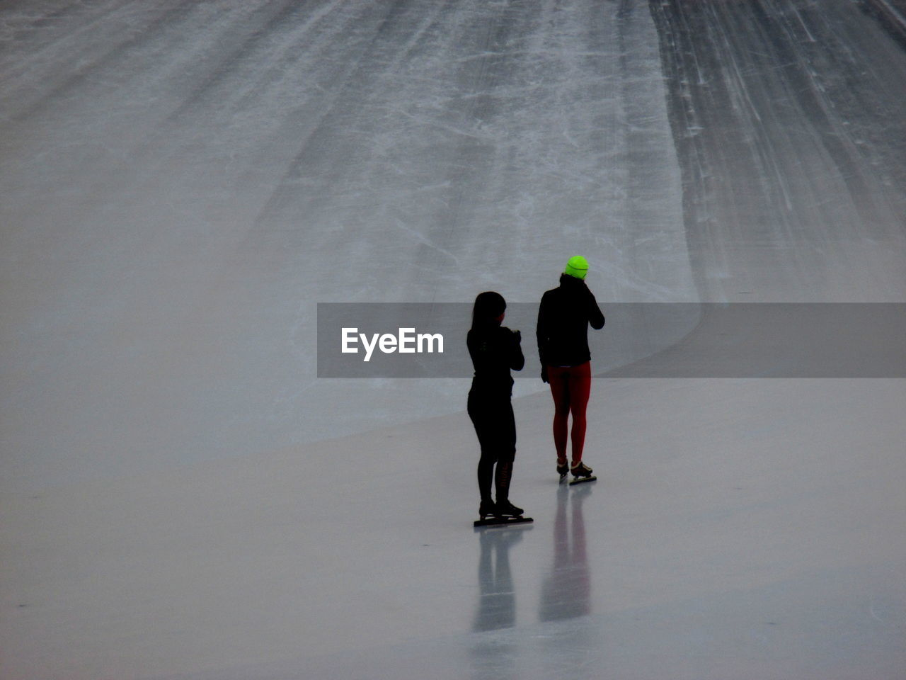 Rear View Of Women Standing On Ice Rink