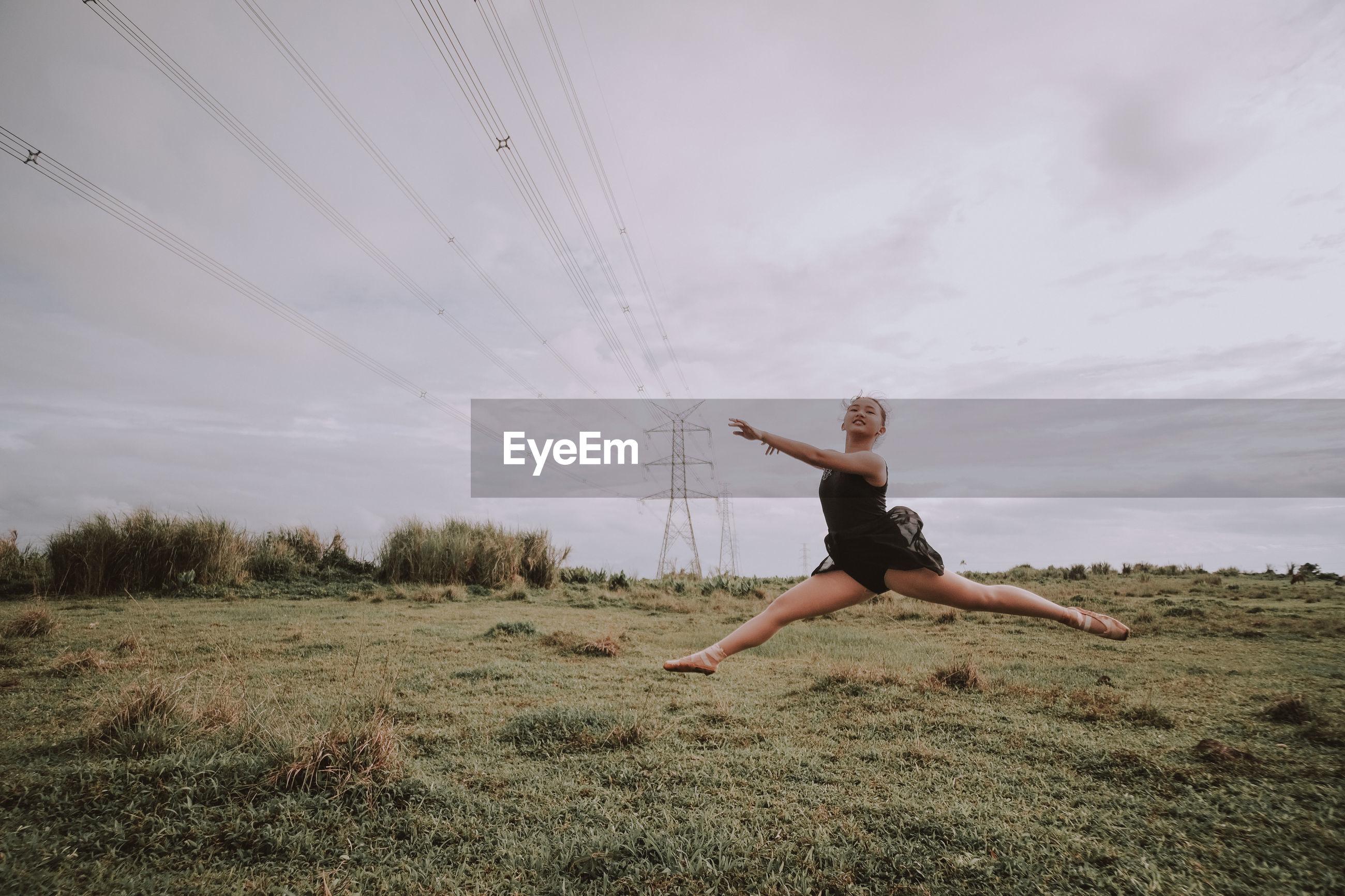 Ballerina jumping on grassy land against sky