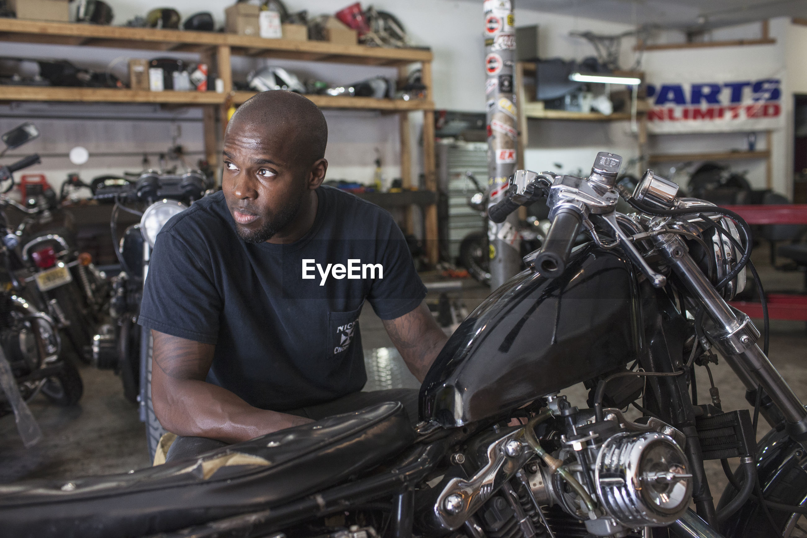 A young man fixing a motorcycle.