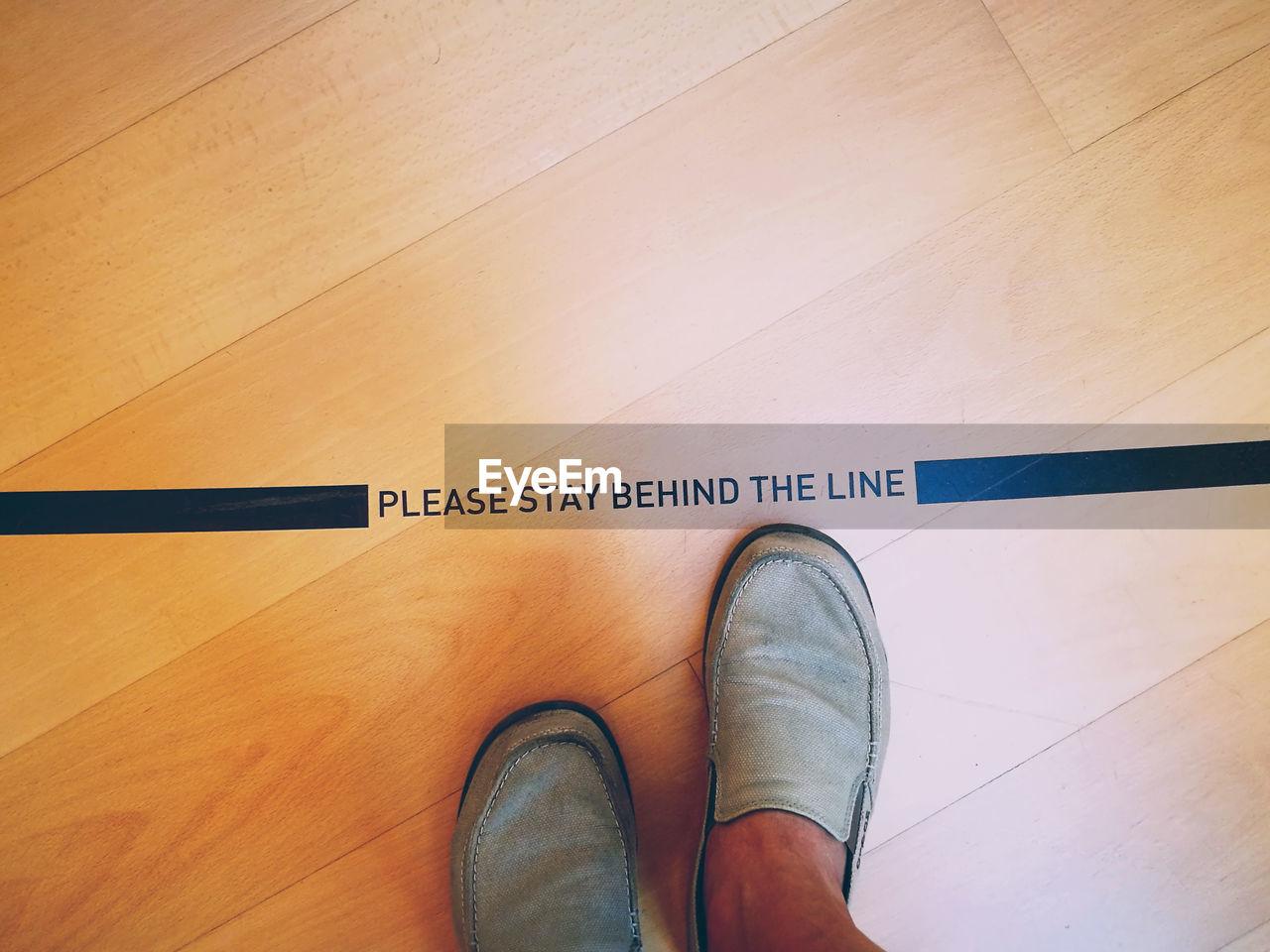 Low Section Of Man Standing On Hardwood Floor