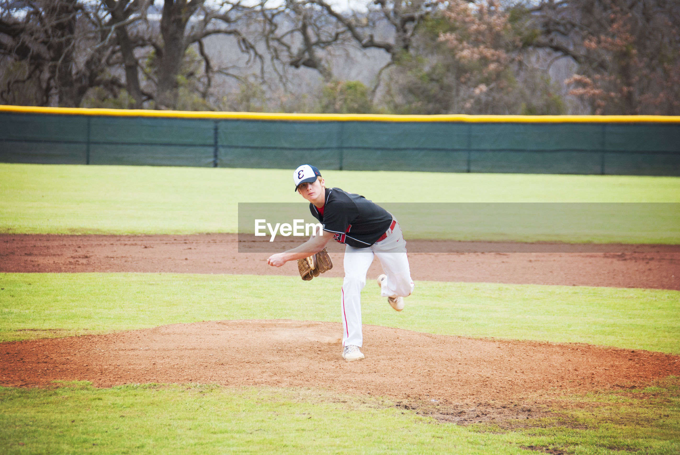 Baseball pitcher throwing on field