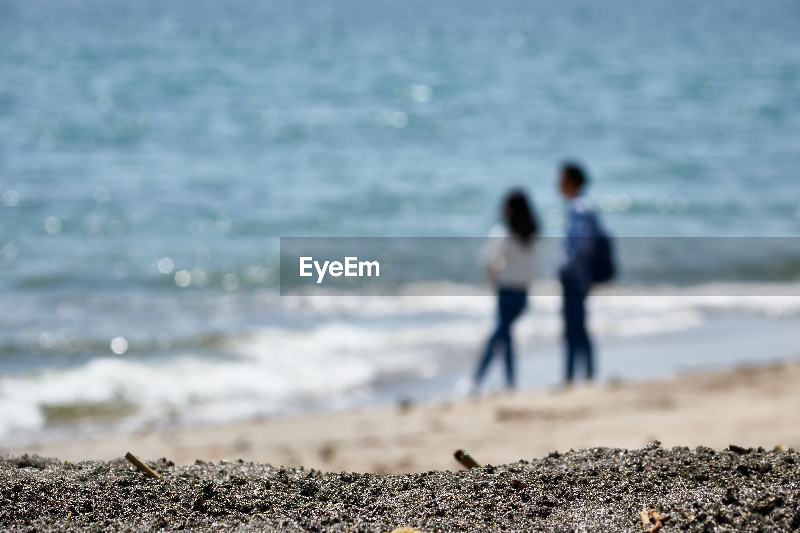 Defocused image of couple standing on shore at beach