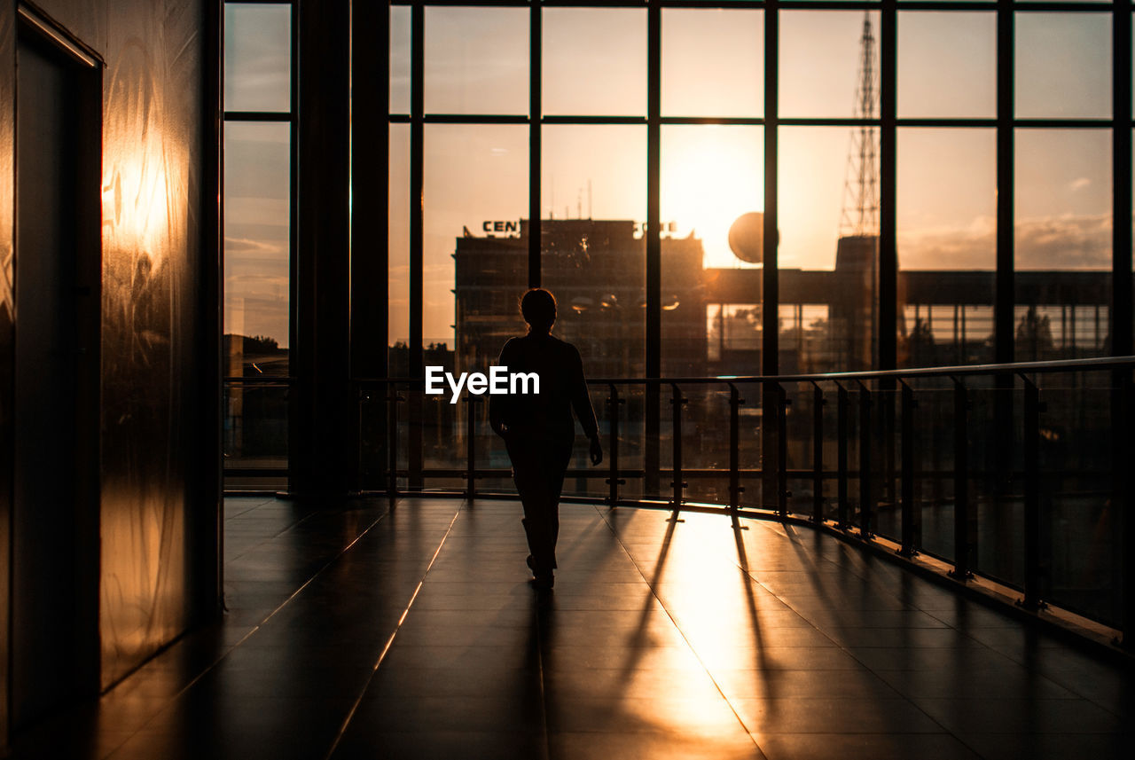 Silhouette Woman Walking In Corridor Of Modern Building Against Sunset