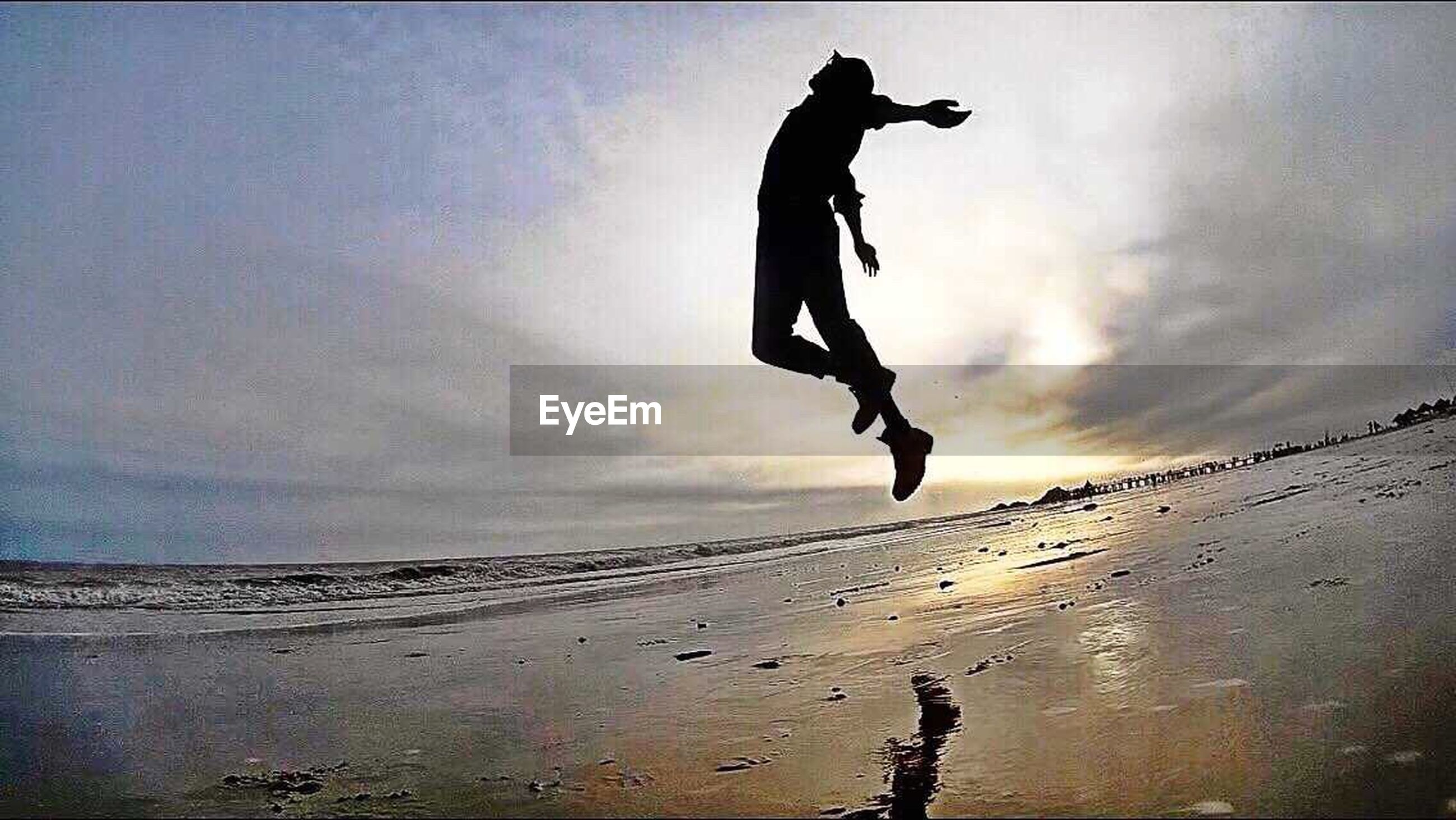 full length, sky, cloud - sky, leisure activity, jumping, lifestyles, mid-air, arms outstretched, balance, men, arms raised, cloud, cloudy, silhouette, low angle view, sea, motion, vitality