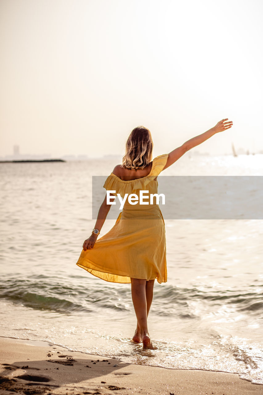 Rear view of woman with arms raised while standing on beach