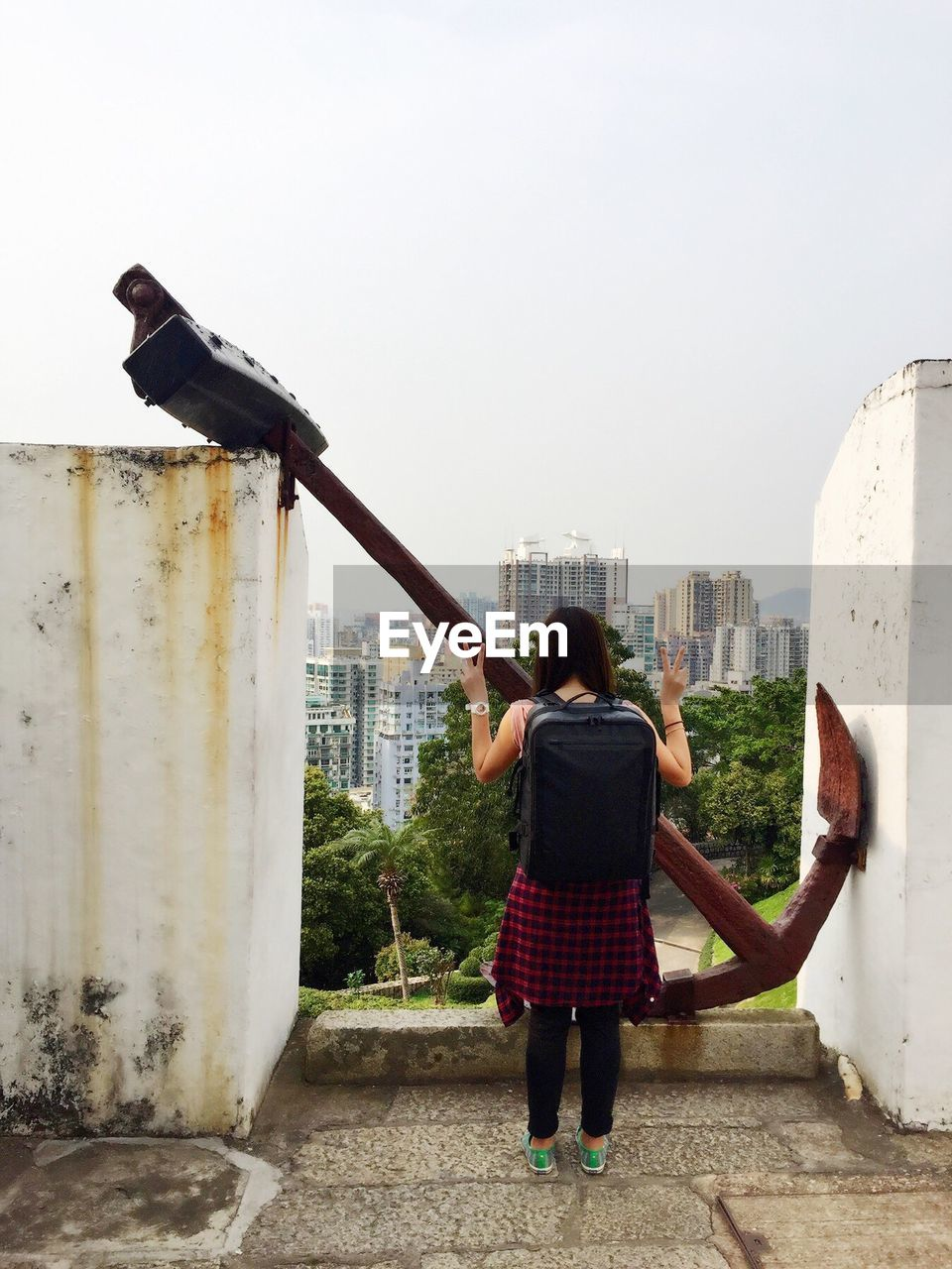 Rear view of woman showing victory sign while standing by rusty anchor on building terrace