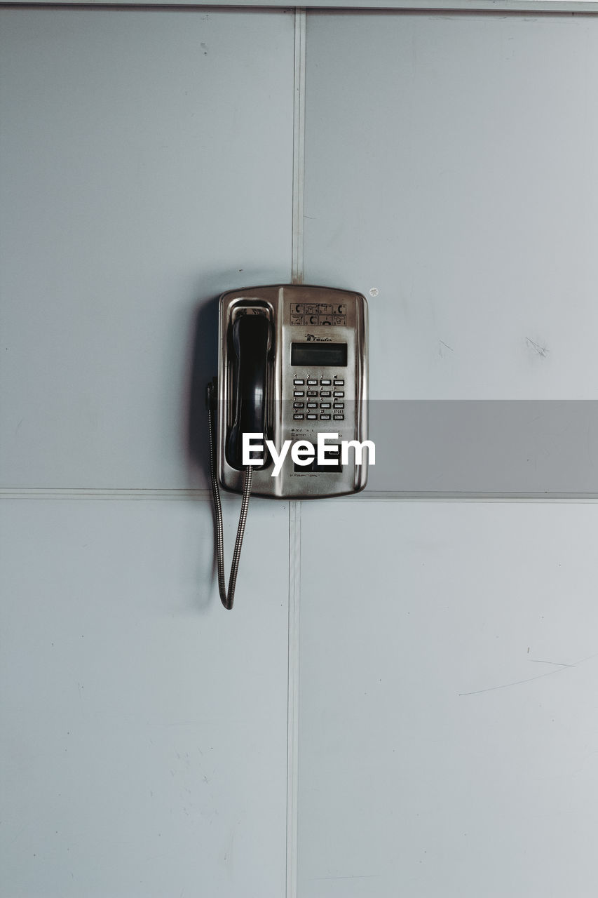 technology, telephone, wall - building feature, indoors, communication, connection, no people, retro styled, pay phone, copy space, telecommunications equipment, close-up, telephone receiver, old, cable, white color, metal, listening, landline phone, power supply