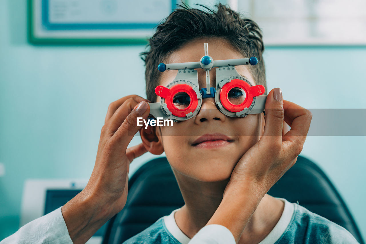 Smiling Ophthalmologist Doing Eye Test Of Boy