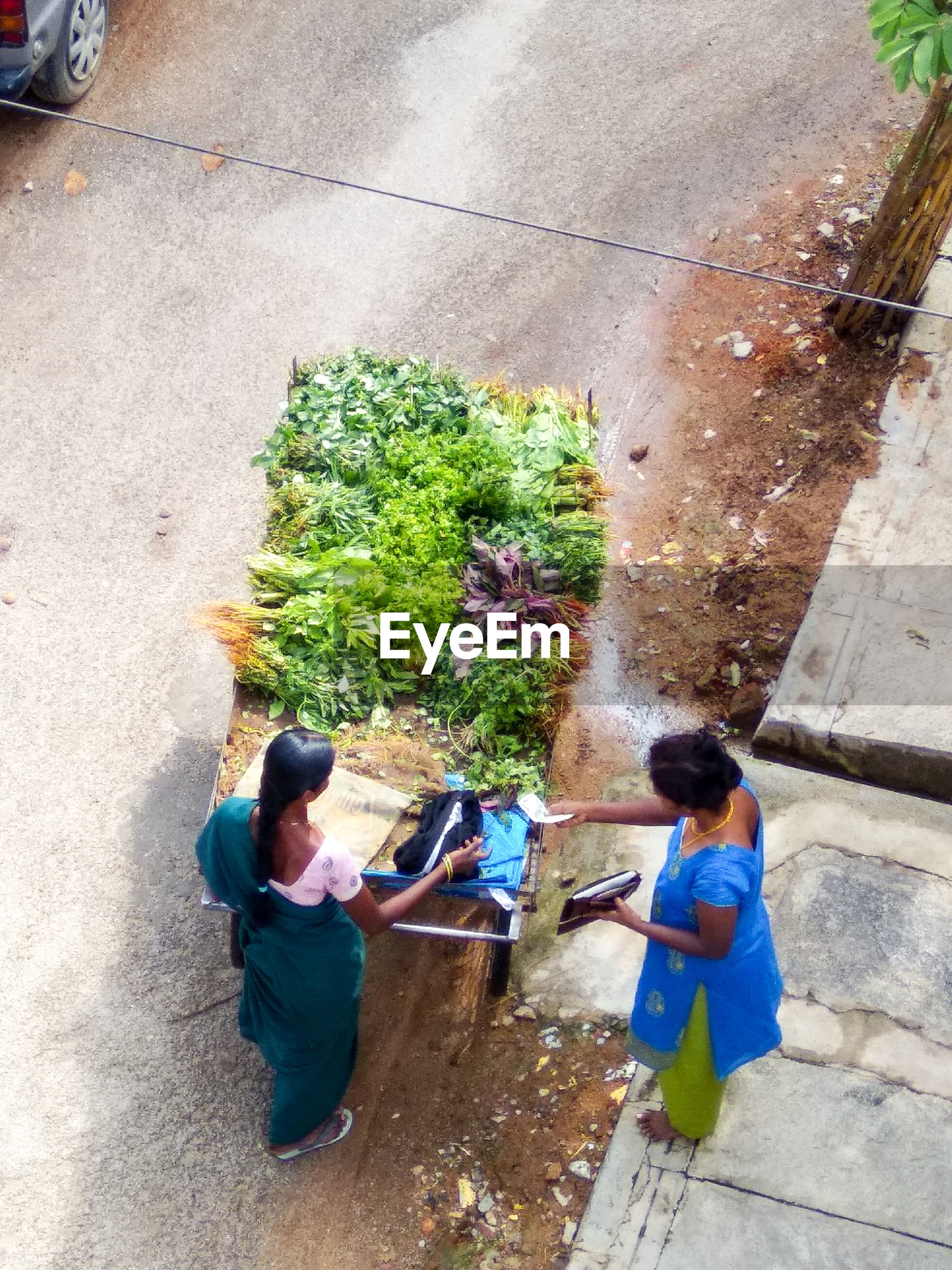High angle view of woman buying vegetables while standing on footpath