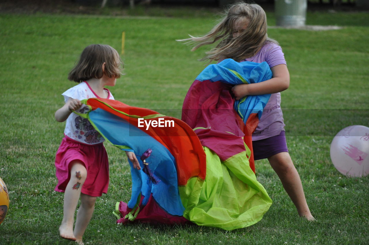 childhood, grass, togetherness, girls, full length, two people, leisure activity, playing, outdoors, day, boys, real people, child, friendship, people