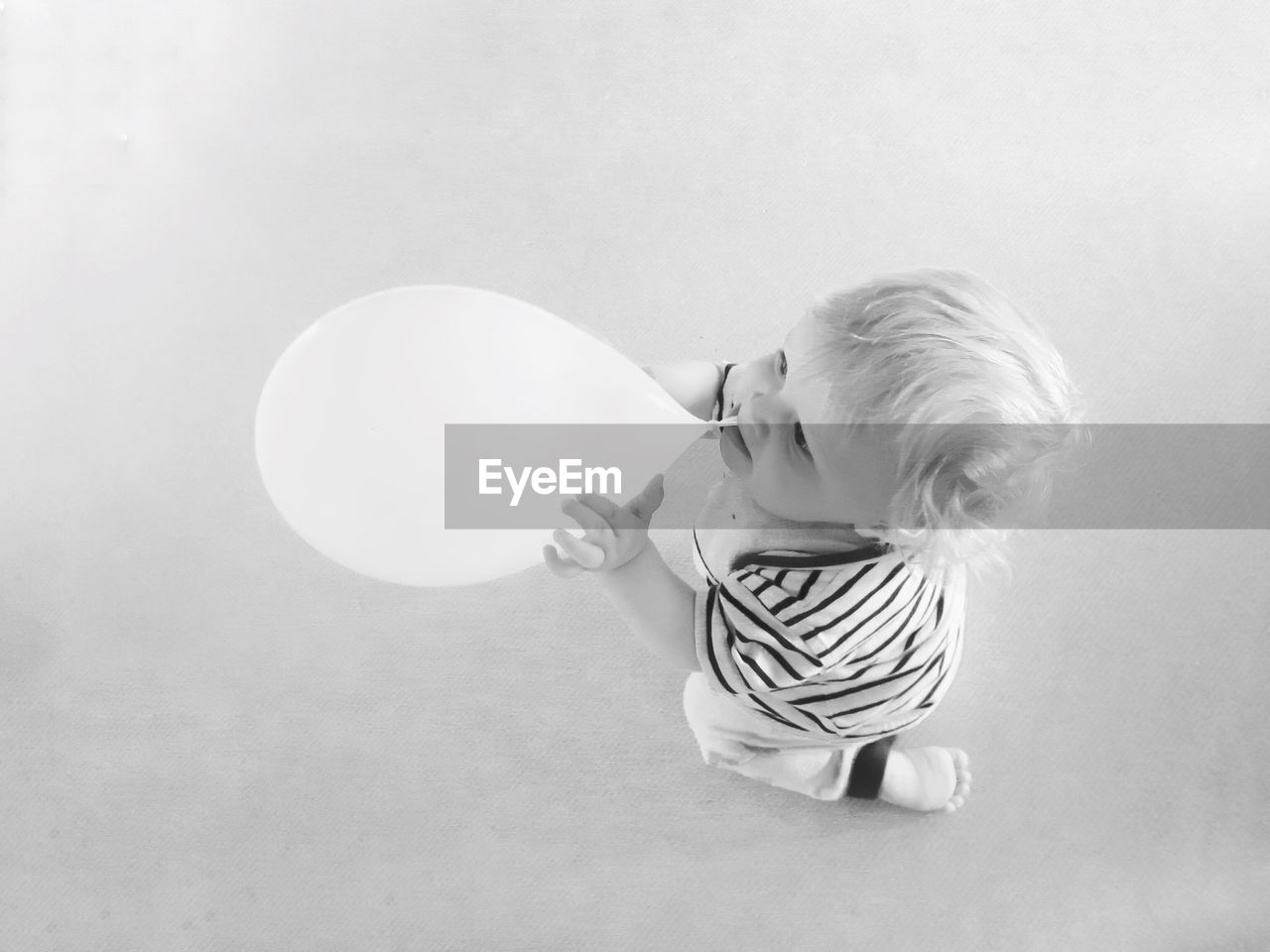 High angle view of baby boy biting balloon against gray background