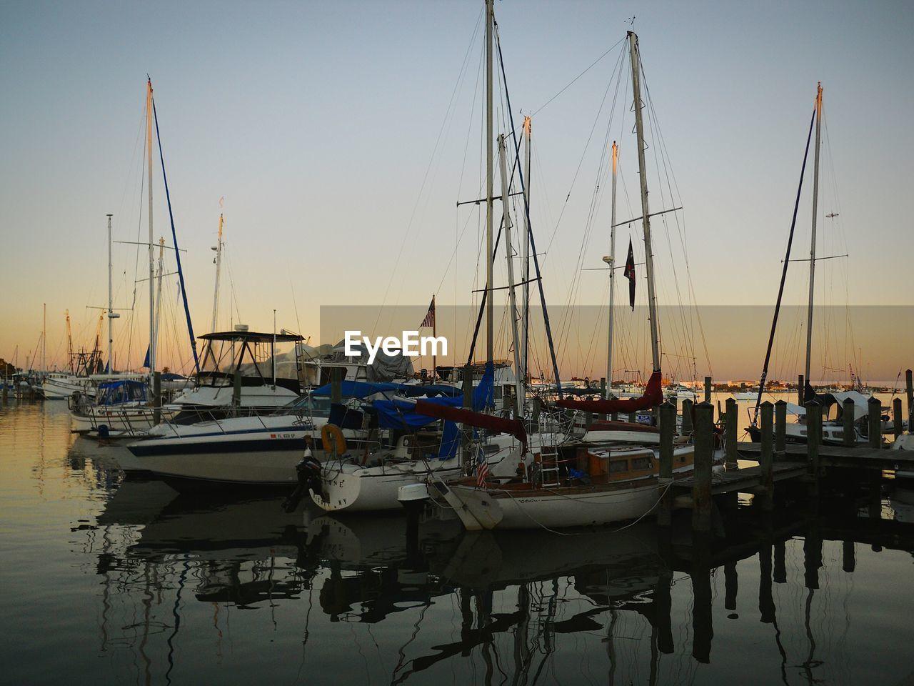 Sailboats Moored At Marina Against Sky During Sunset