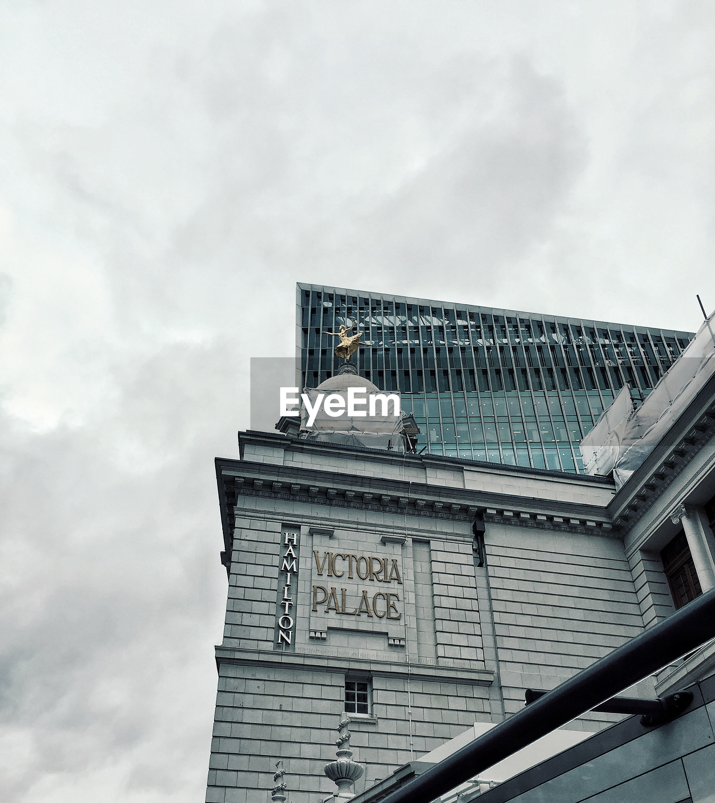 HIGH SECTION OF BUILDING AGAINST CLOUDY SKY