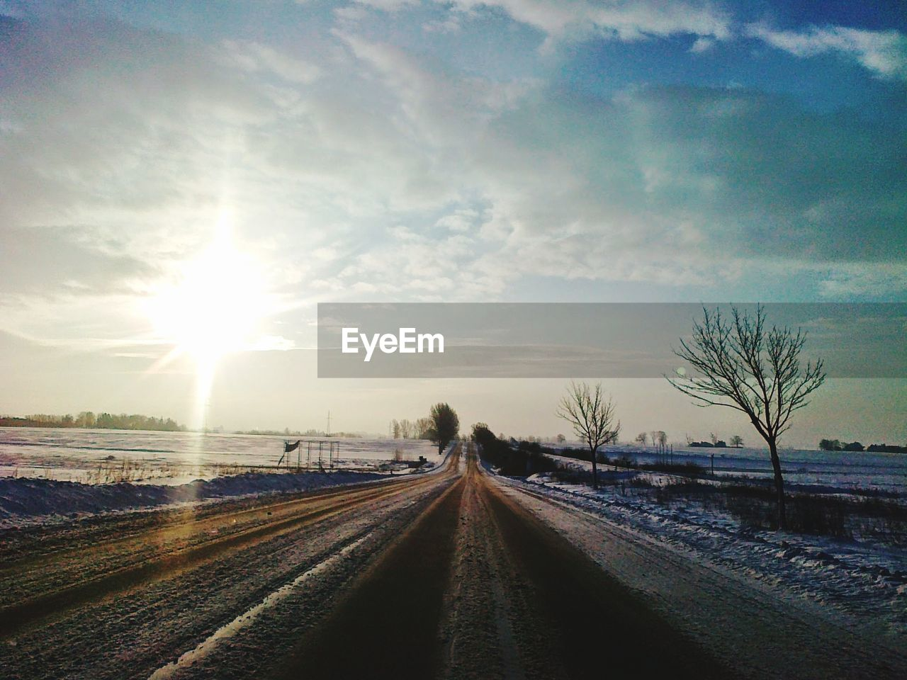 sky, cloud - sky, nature, transportation, snow, the way forward, direction, tree, sunlight, sun, road, winter, no people, cold temperature, plant, diminishing perspective, vanishing point, beauty in nature, field, outdoors, lens flare