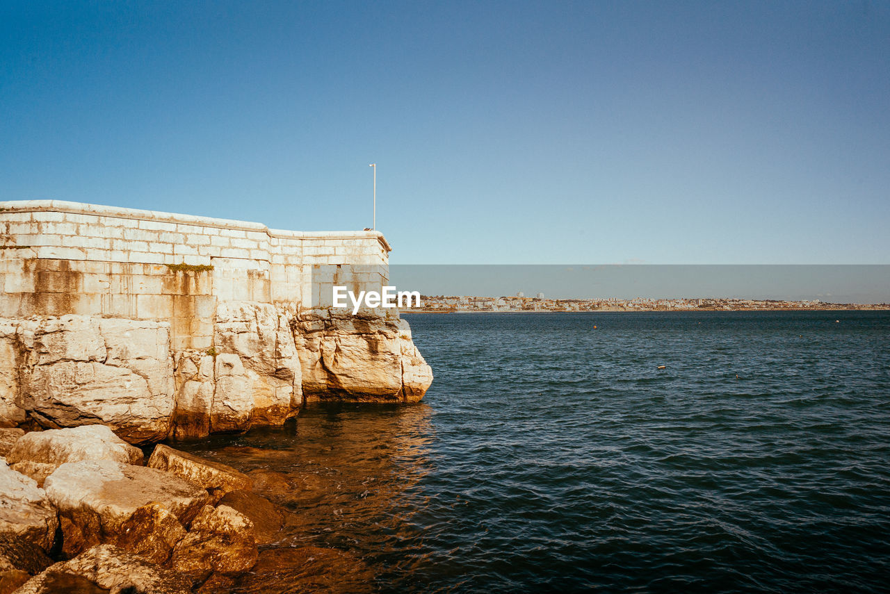 sky, clear sky, water, copy space, sea, rock, nature, rock - object, day, solid, waterfront, blue, no people, architecture, scenics - nature, beauty in nature, outdoors, sunlight, tranquil scene