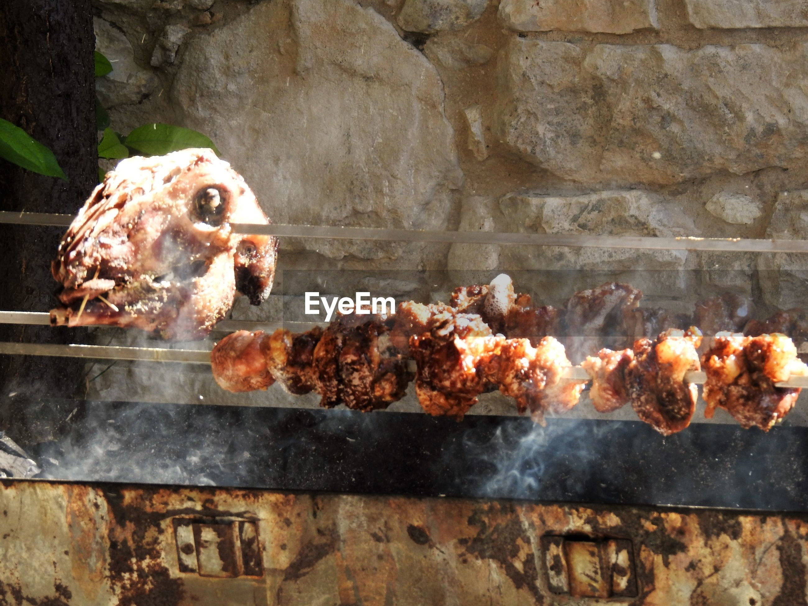 Close-up of meat in skewer on barbecue grill