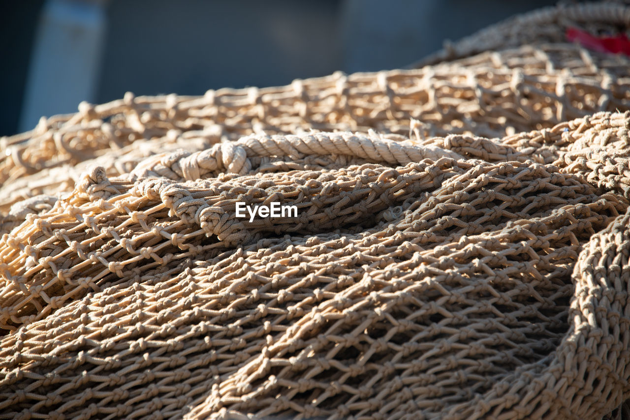 rope, close-up, pattern, no people, focus on foreground, strength, still life, day, sunlight, textured, selective focus, nature, outdoors, water, transportation, brown, jute, high angle view, connection, tied up, fishing industry