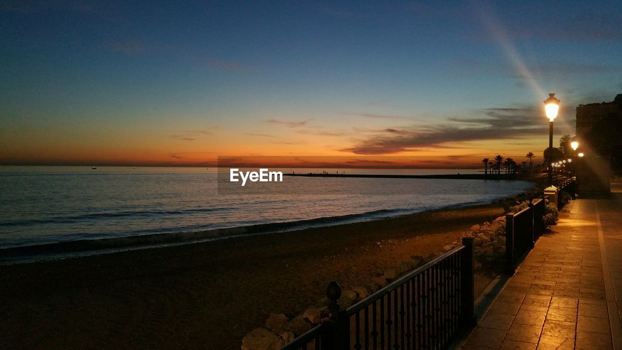 sea, sunset, water, horizon over water, nature, scenics, sky, tranquil scene, railing, beauty in nature, beach, tranquility, outdoors, vacations, no people, architecture, animal themes, day