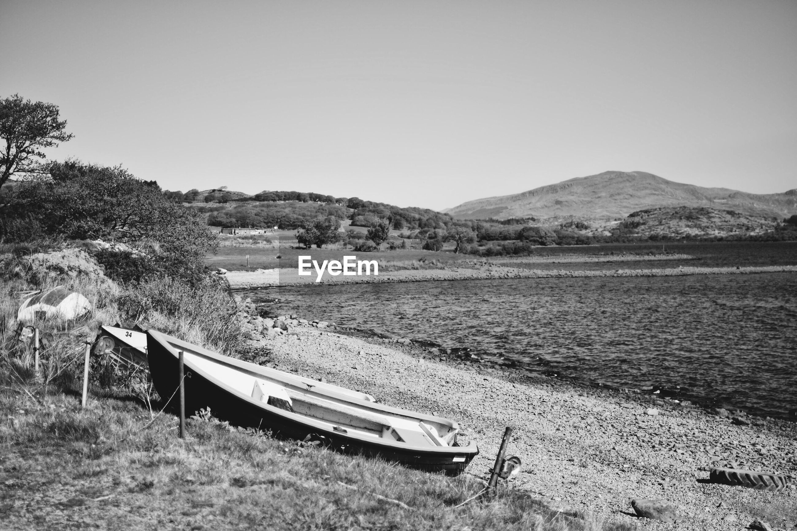 BOAT MOORED ON FIELD BY MOUNTAIN AGAINST CLEAR SKY