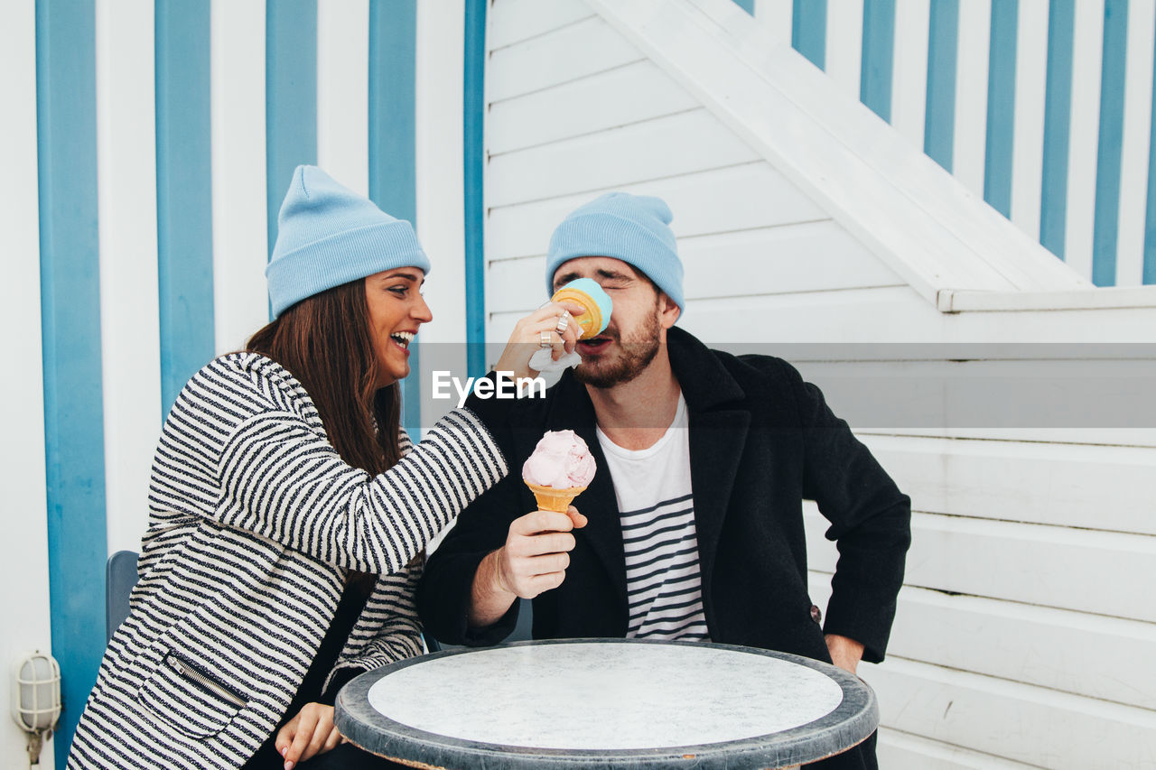 food and drink, togetherness, front view, two people, young adult, casual clothing, happiness, leisure activity, hat, adult, lifestyles, young women, women, smiling, holding, real people, emotion, food, bonding, couple - relationship, outdoors