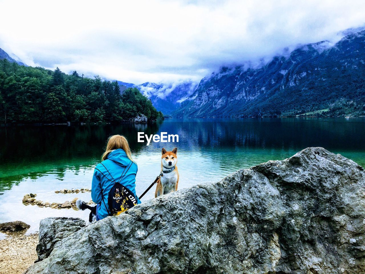 Rear view of mid adult woman with dog sitting on rock at lakeshore against cloudy sky