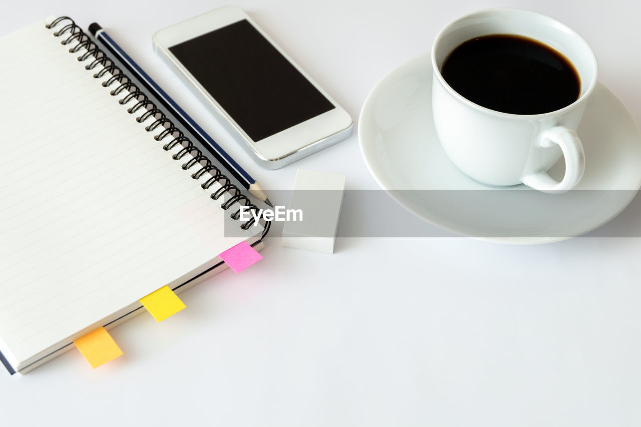 HIGH ANGLE VIEW OF COFFEE CUP ON BOOK