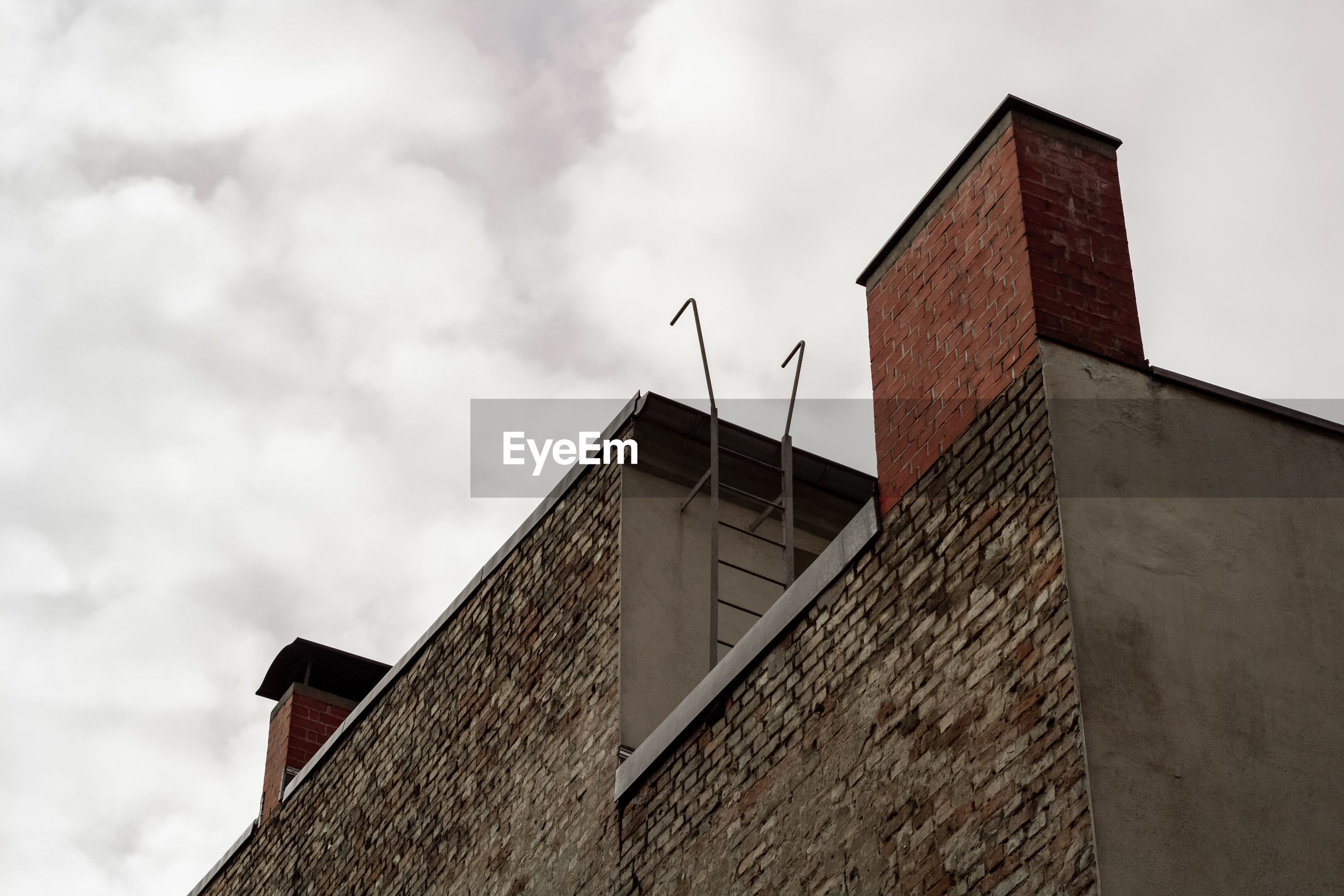 Low angle view of building with chimneys against cloudy sky