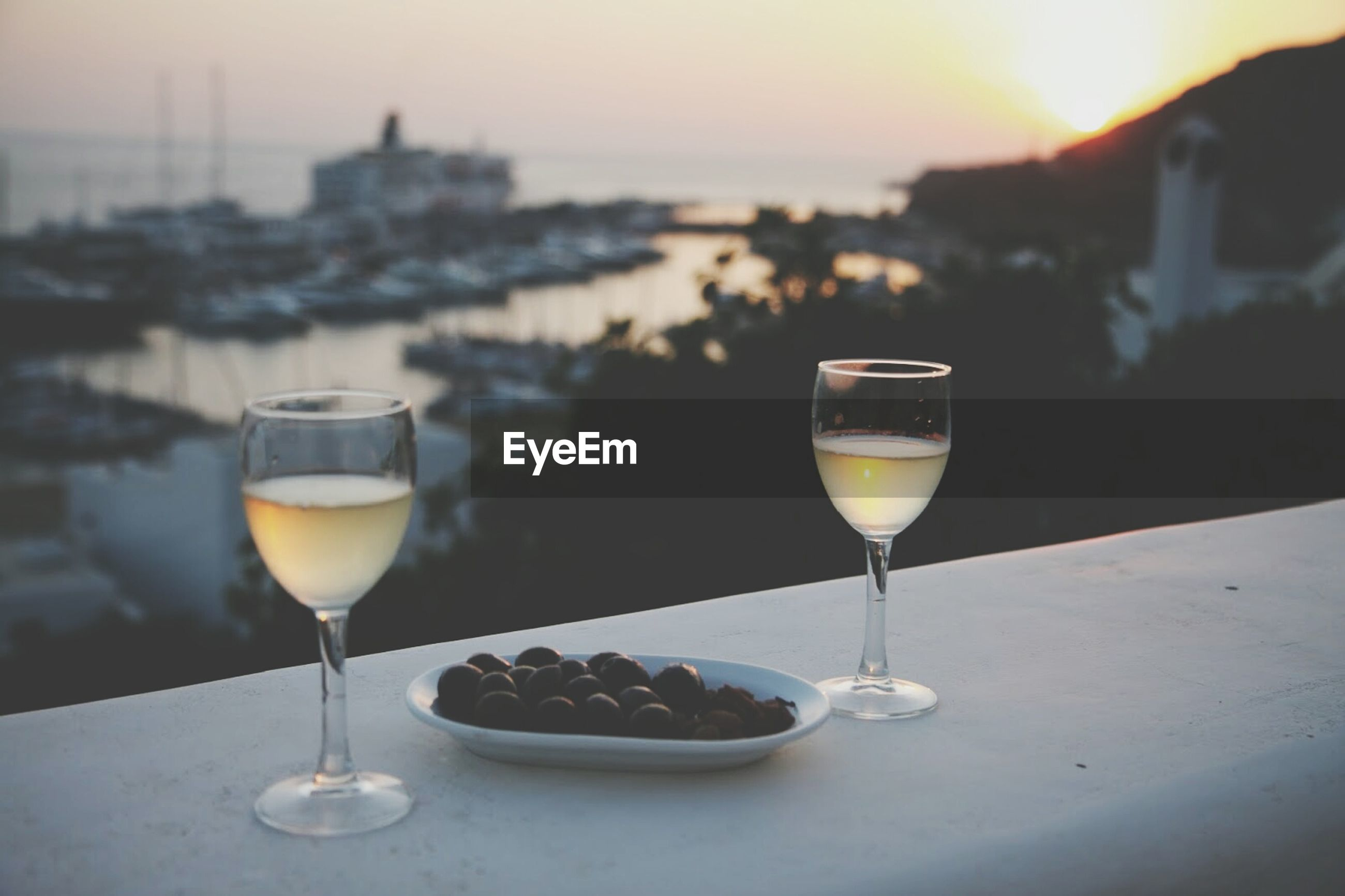 Black olives and wine glasses on balcony