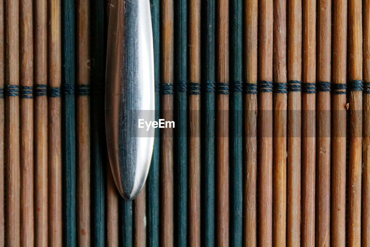 Close-Up Of Spoon On Straw Mat