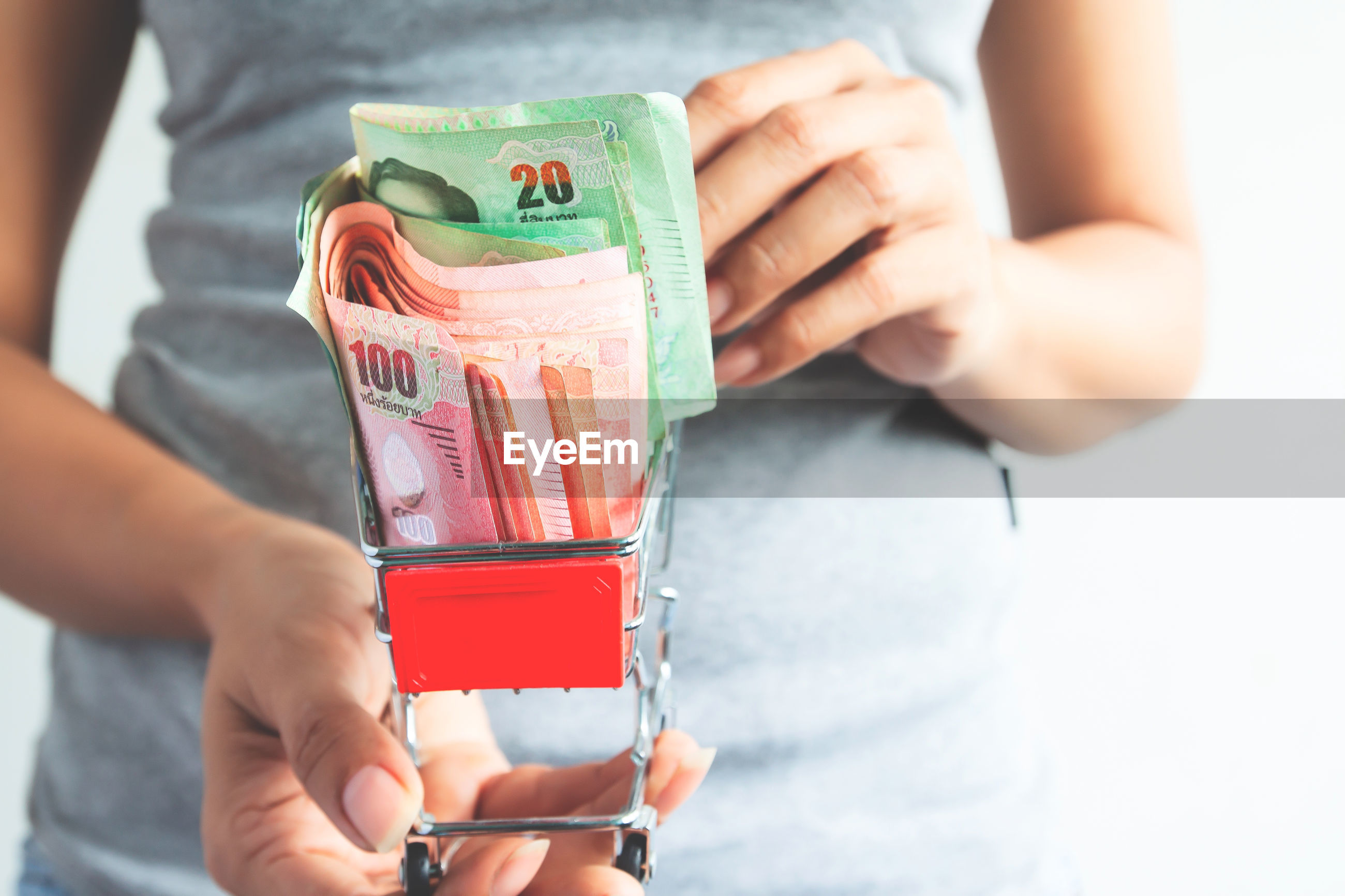 Midsection of woman holding currency in miniature shopping cart against white background