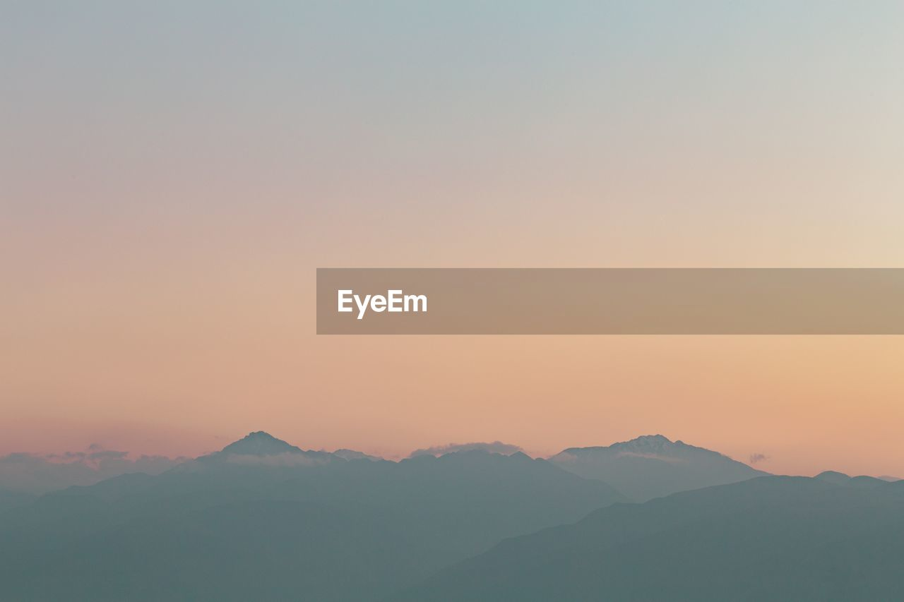 beauty in nature, mountain, scenics - nature, sky, tranquility, tranquil scene, sunset, non-urban scene, mountain range, idyllic, environment, no people, nature, orange color, clear sky, copy space, landscape, remote, outdoors, mountain peak, hazy