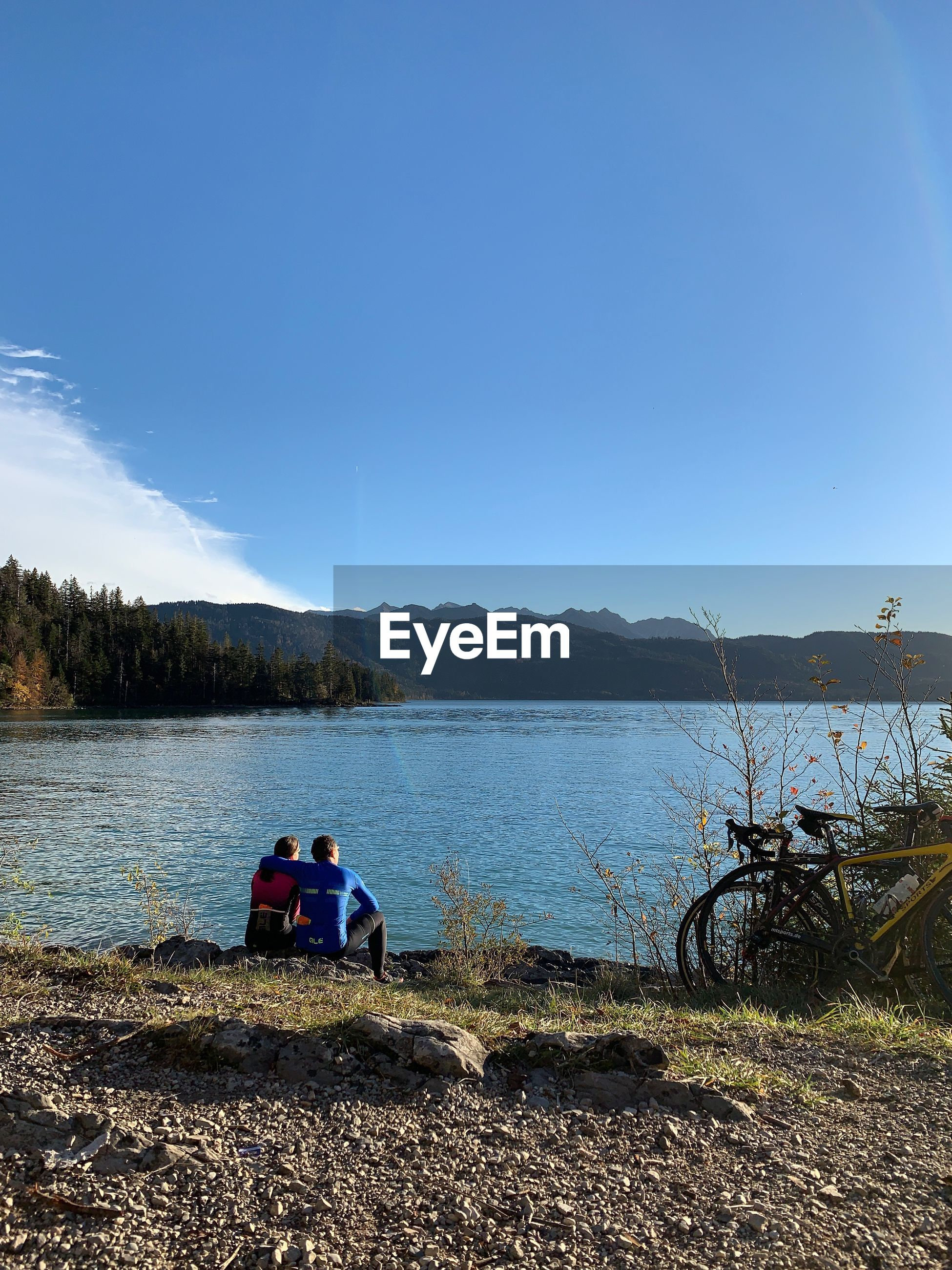 Rear view of couple sitting by lake against blue sky