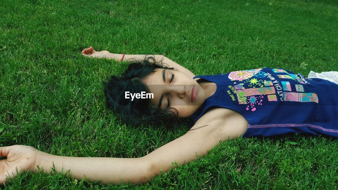 Young Girl Lying On Grassy Field