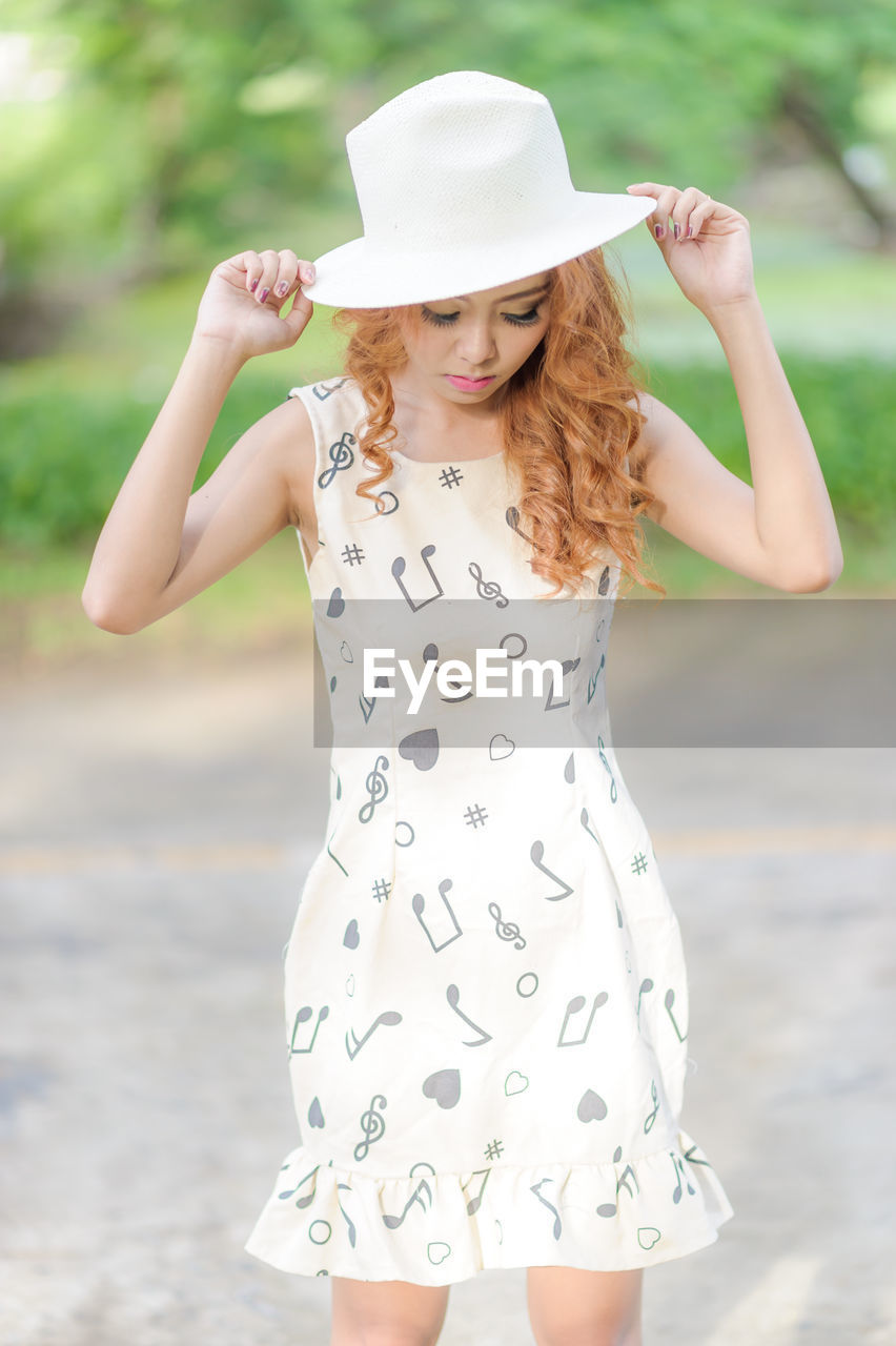one person, young women, standing, women, clothing, front view, hat, real people, lifestyles, leisure activity, beauty, beautiful woman, three quarter length, focus on foreground, fashion, casual clothing, young adult, looking at camera, hair, hairstyle, outdoors