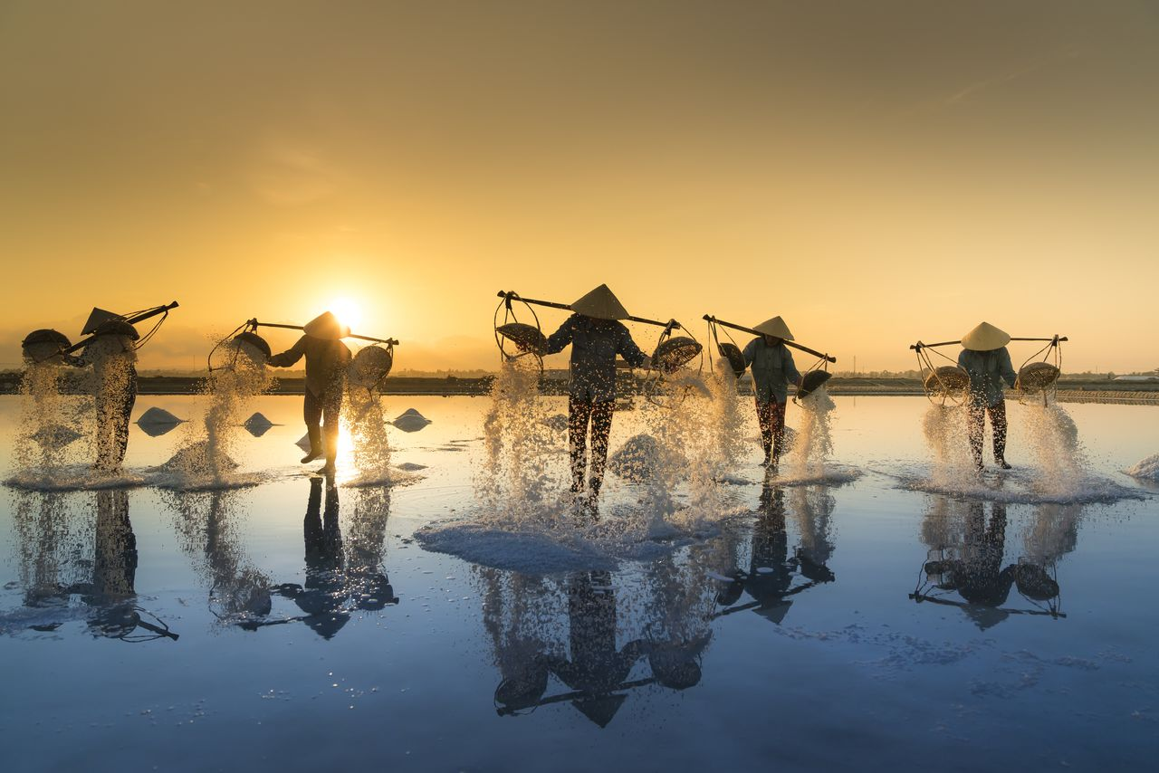 Men Pouring Water From Containers In Lake Against Sky During Sunset