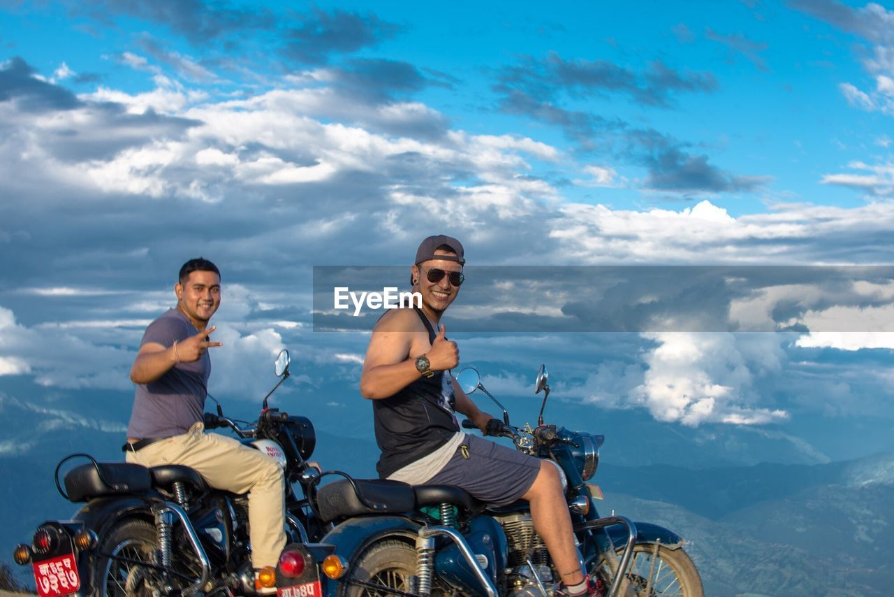 FRIENDS RIDING MOTORCYCLE AGAINST SKY