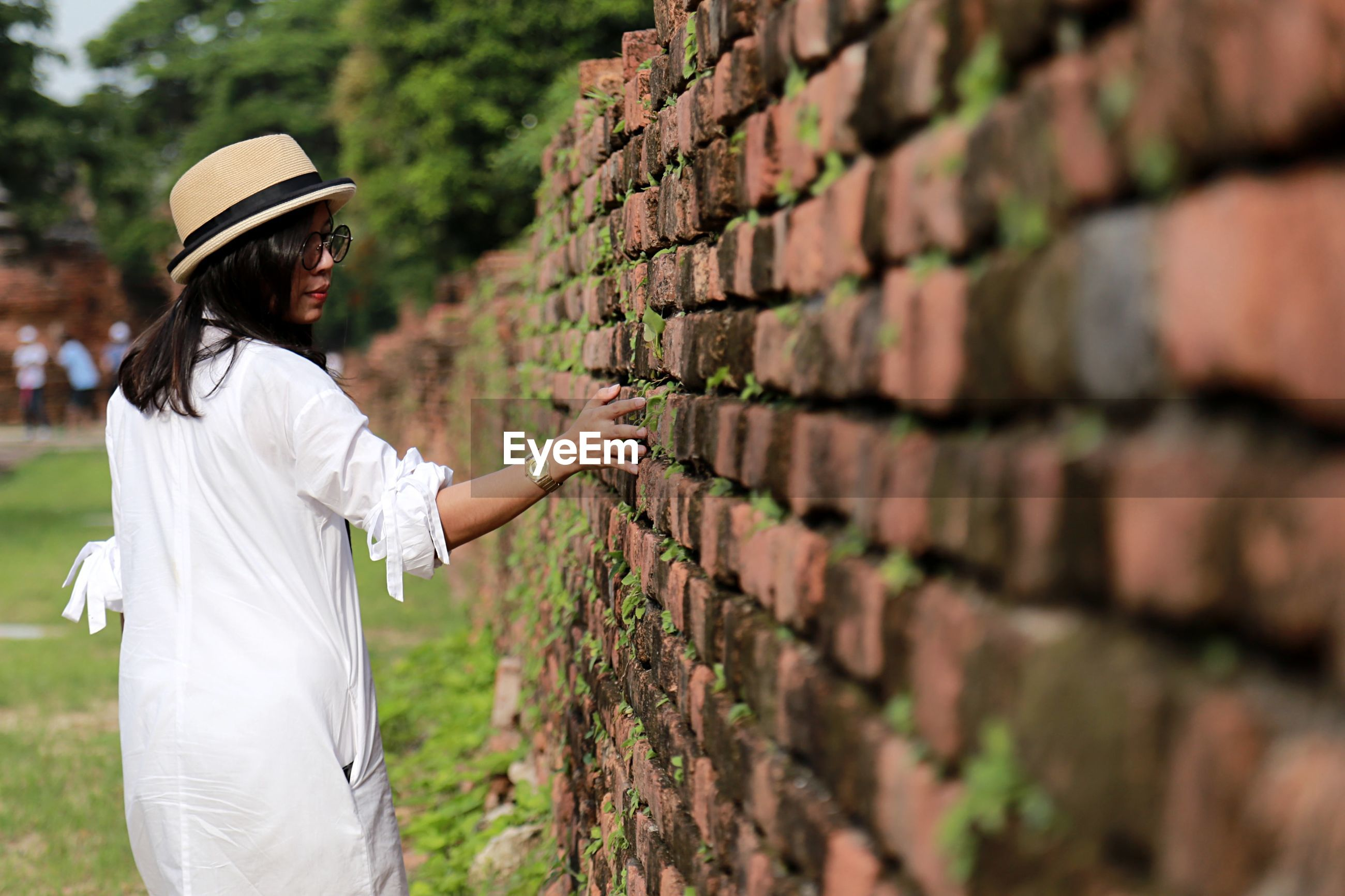 Rear view of woman touching brick wall while walking outdoors