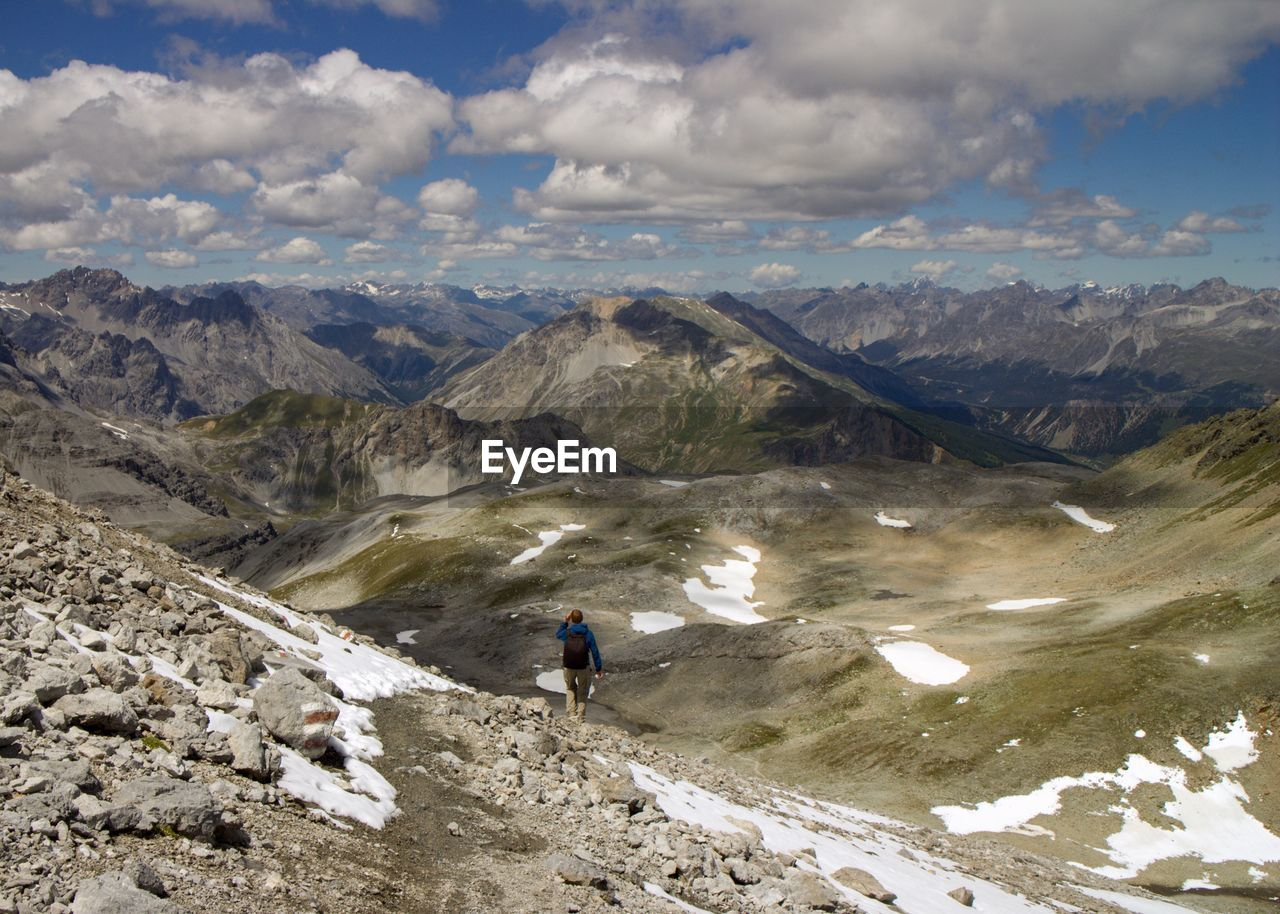 Rear view of hiker on mountain against sky