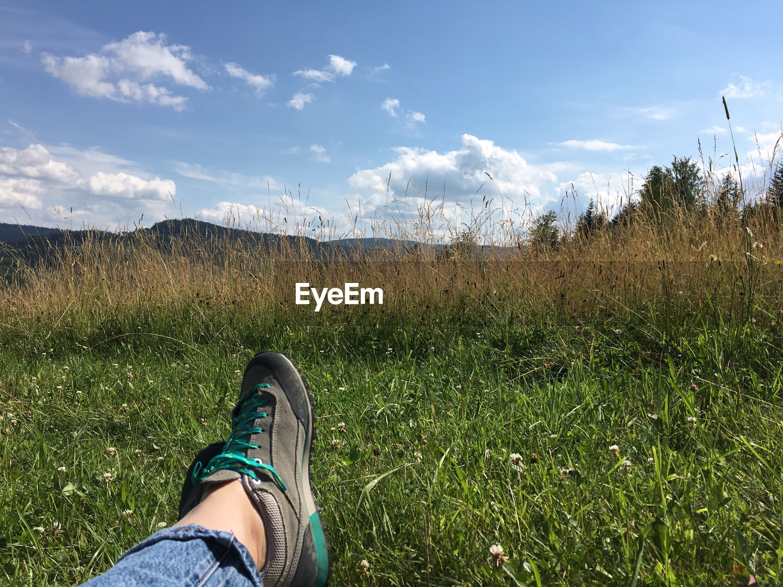 grass, one person, human leg, low section, personal perspective, cloud - sky, sky, field, shoe, growth, nature, day, standing, real people, outdoors, landscape, adventure, lifestyles, human body part, beauty in nature, scenics, people
