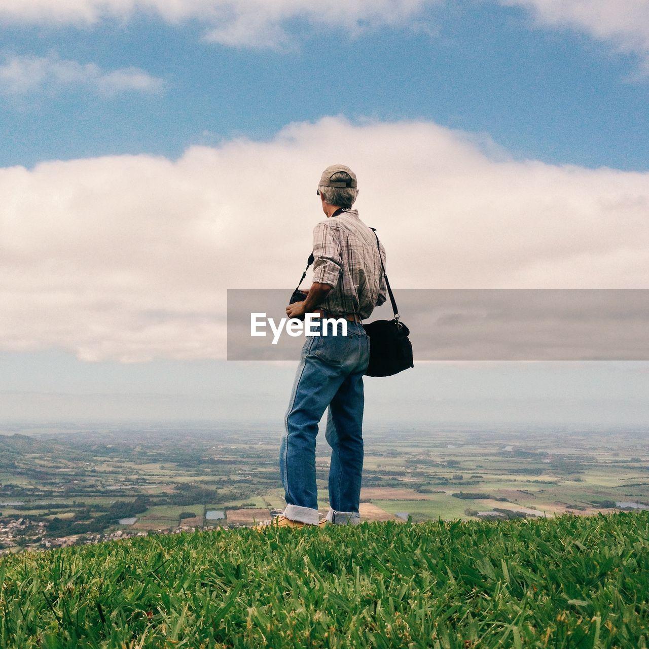 Full Length Of Man Standing On Grass Against Sky