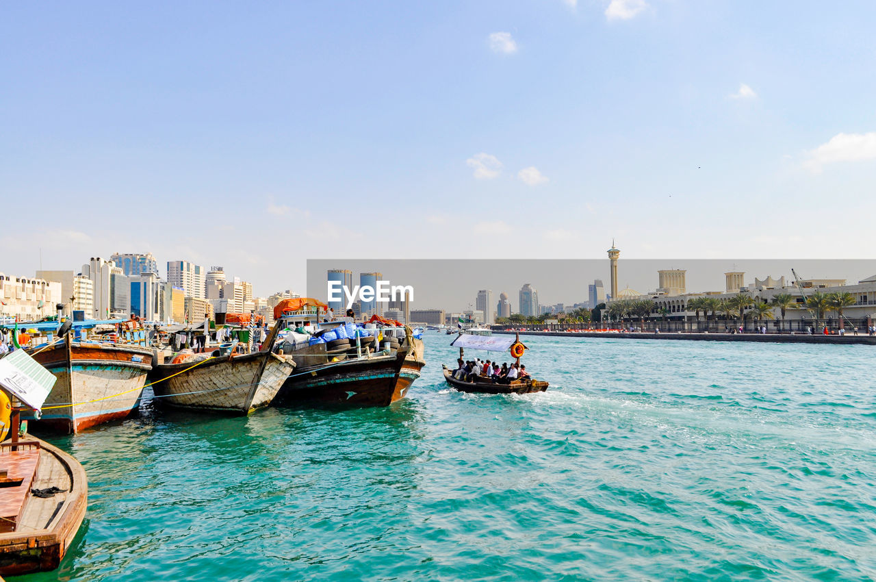 transportation, nautical vessel, mode of transport, architecture, building exterior, built structure, city, skyscraper, waterfront, water, sky, cityscape, outdoors, day, sea, urban skyline, nature, no people