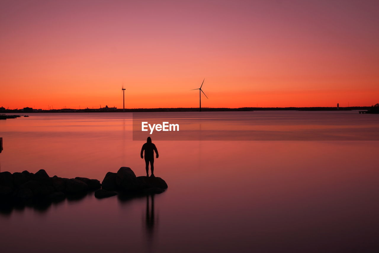 Silhouette of wind turbines against sky during sunset